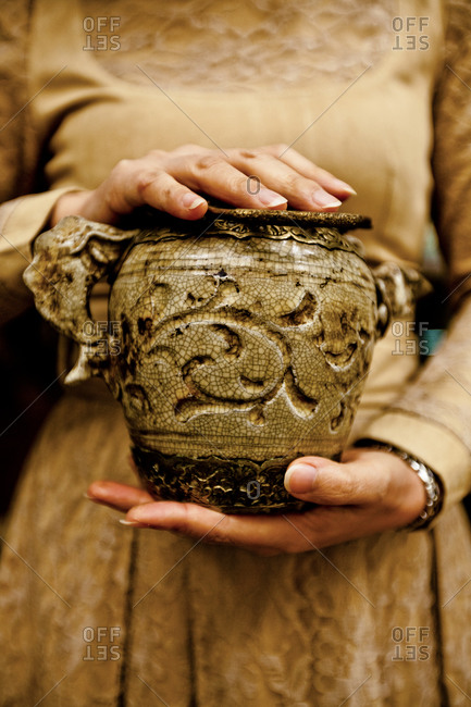 Woman holding replica of an old teapot in Hanoi, Vietnam