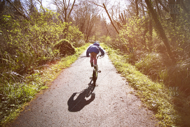 Child standing on bike seat on a sunny wooded path