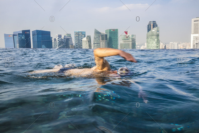 January 22, 2015: Man swimming in hotel infinity pool in Singapore