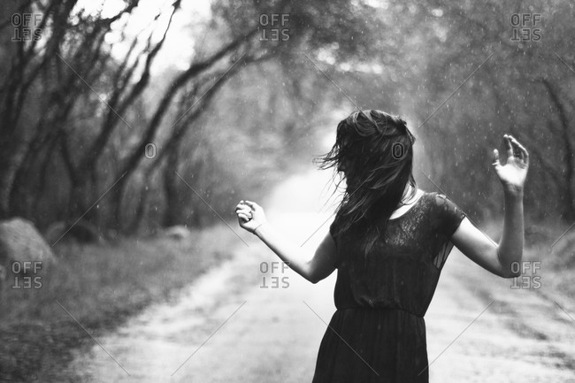 Woman carefree in rain on country road
