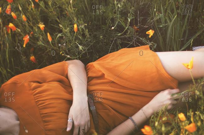 Woman lying in sun dappled field of flowers