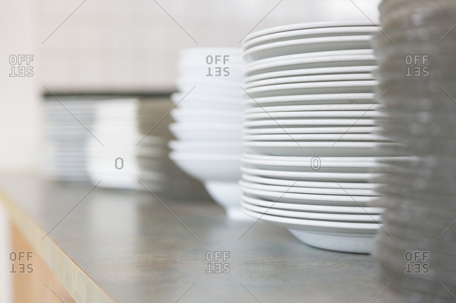 Close up of stacks of plates on a counter
