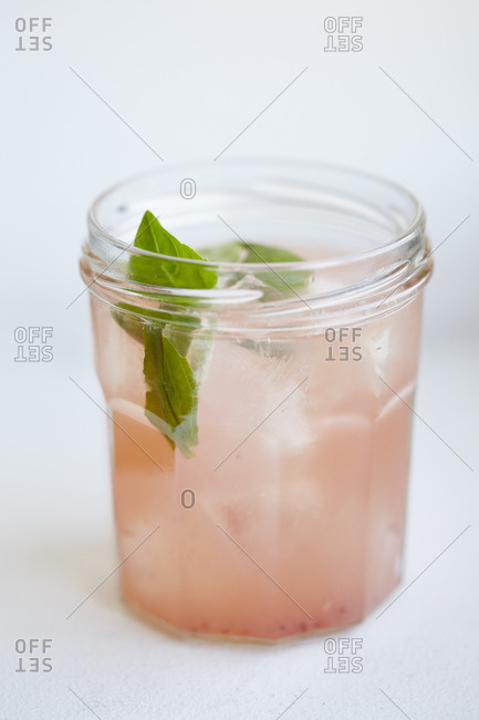 A pink cocktail with basil leaves