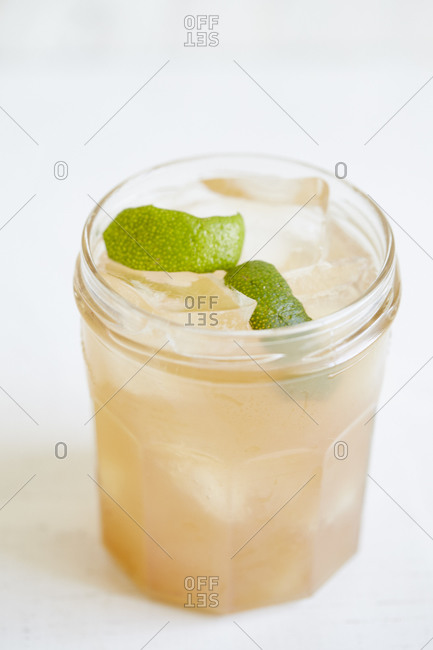 A pale peach cocktail with a lime twist