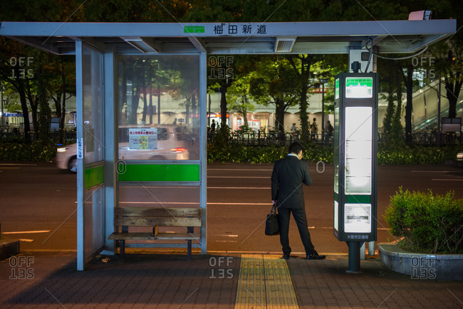 April 24, 2015: A businessman at a bus stop in the neighborhood of Sonezaki in Osaka, Japan