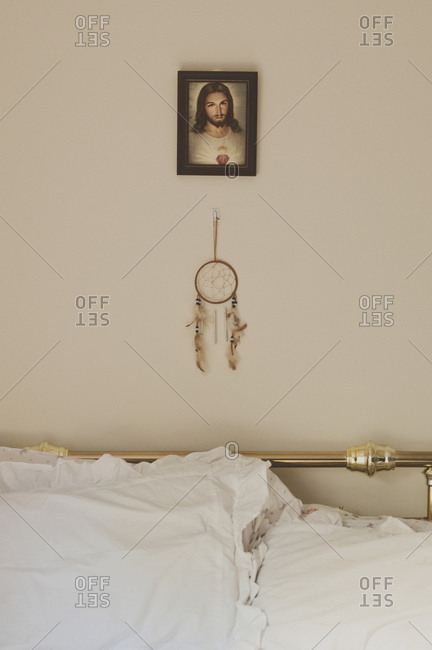 Portrait of Jesus and a dream catcher hang on the bedroom wall behind the bed