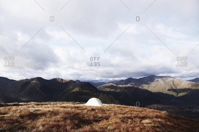 A solitary tent set up at the peak of one rolling mountain in a range