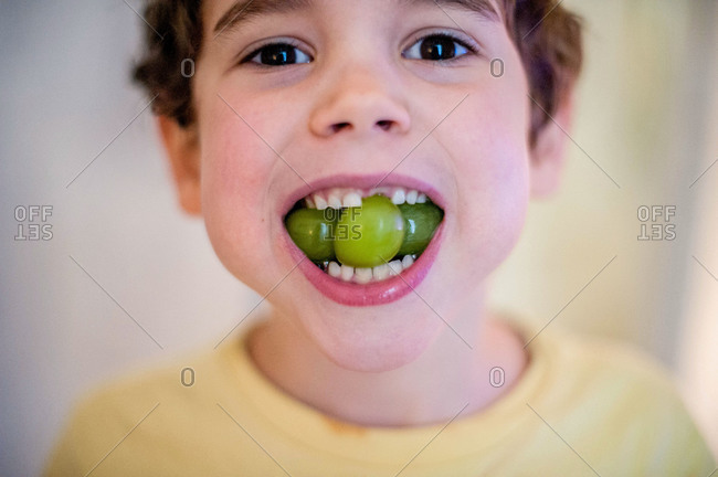 Young boy eating ripe grapes