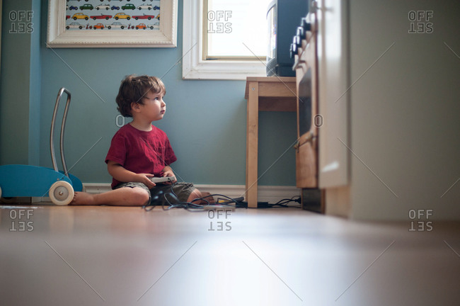 Young boy playing video games on the floor