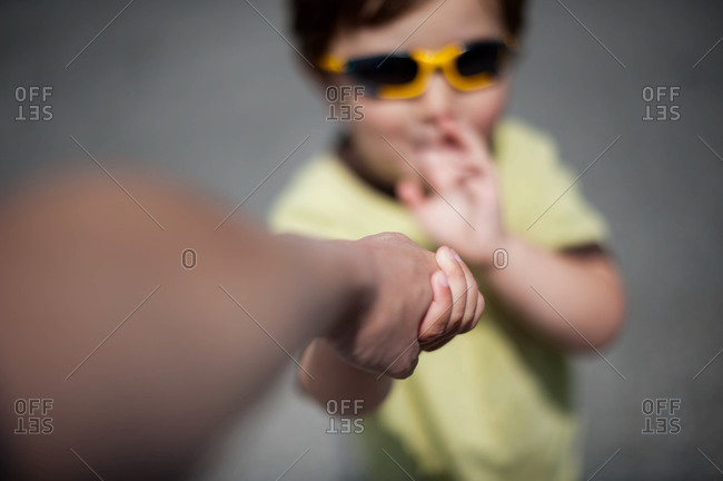 Little boy holding his parent's hand