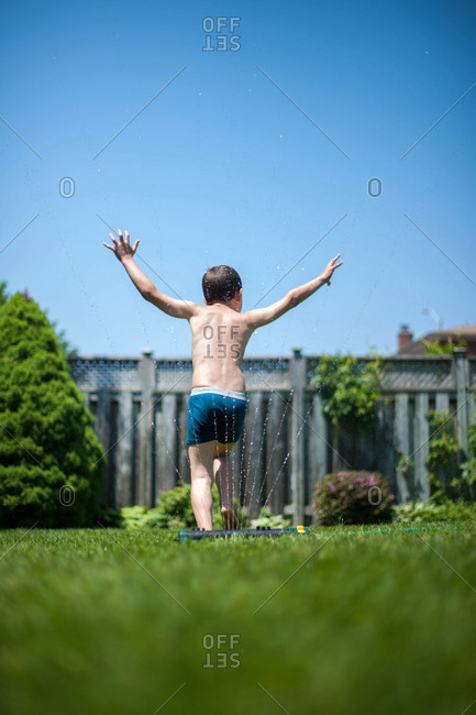 Carefree boy playing at a sprinkler
