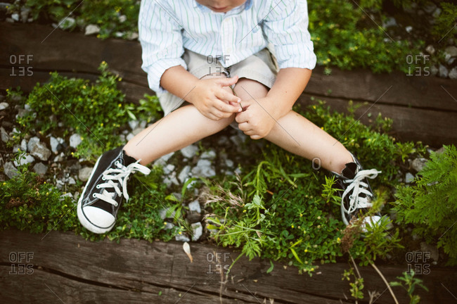 Young boy sitting in a garden