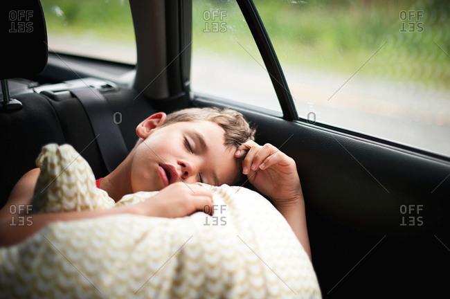 Young boy sleeping in a car