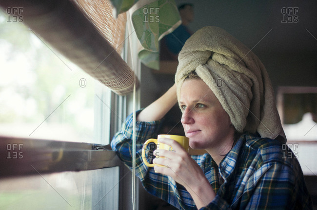 Woman drinking a cup of coffee after a shower