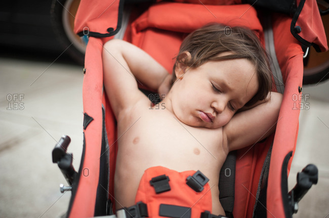 Little boy sleeping in a stroller