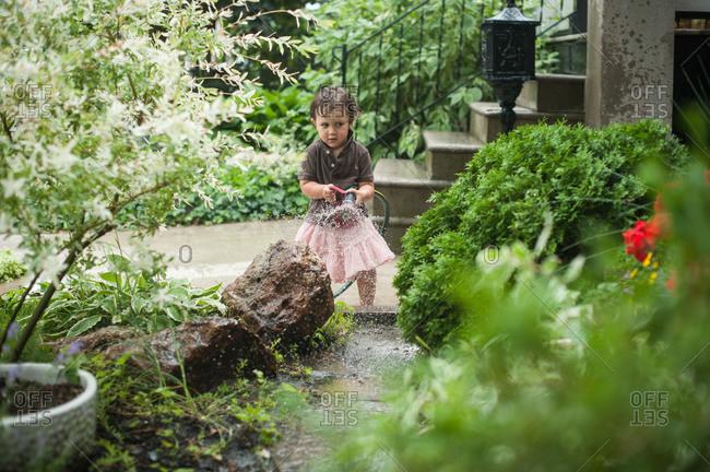 Little boy in pink skirt watering plants in the garden