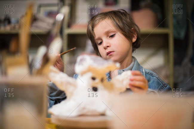 Boy painting a sculpture in a workshop