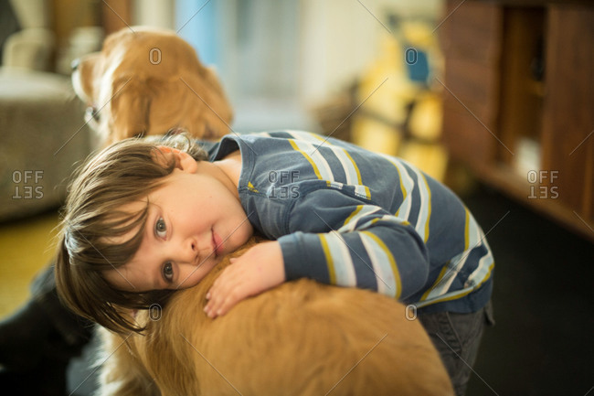 Boy resting his head on a dog