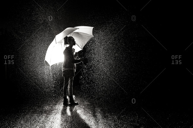 A little girl holds an umbrella in pouring rain