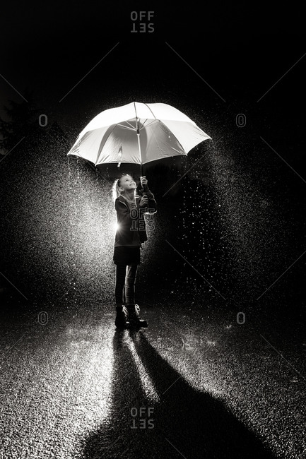 A little girl smiles while holding an umbrella in pouring rain