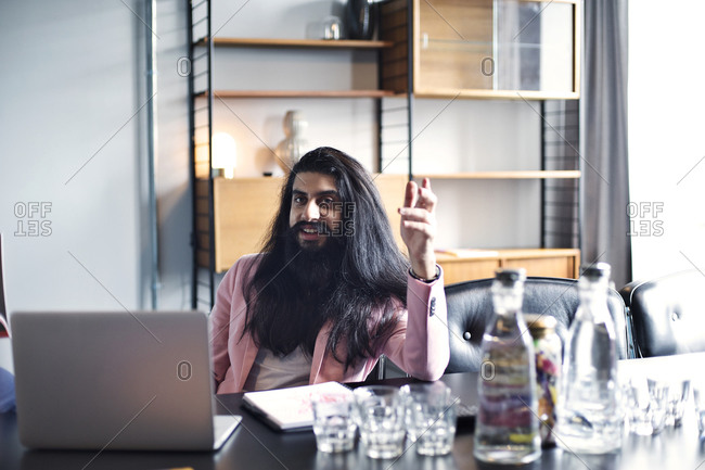 A bearded man sits in an open office with a laptop