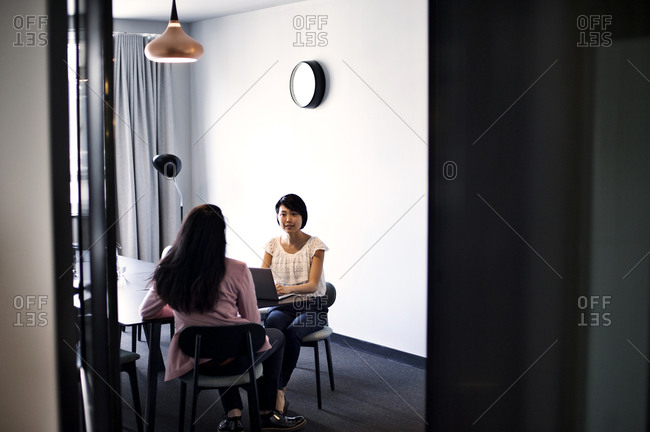 Two colleagues meet in a conference room