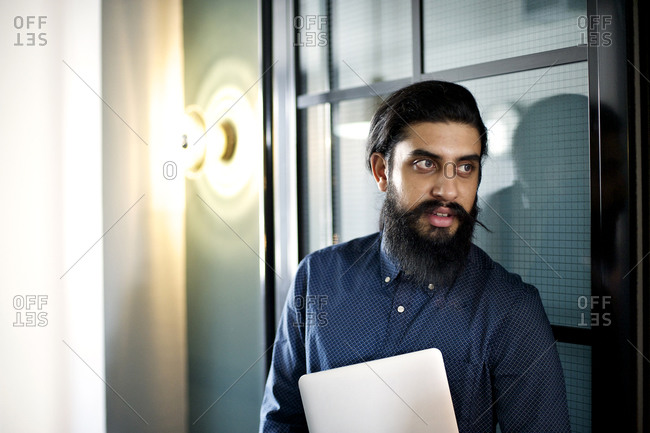 A bearded man turns in the doorway of an office