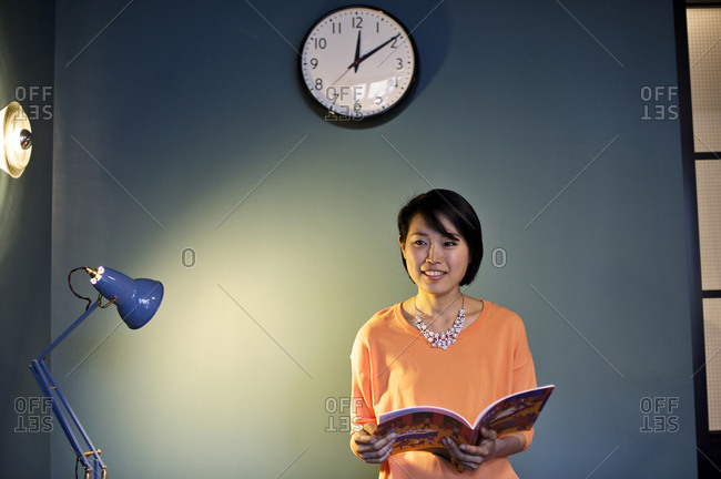 A woman flips through a magazine in an office