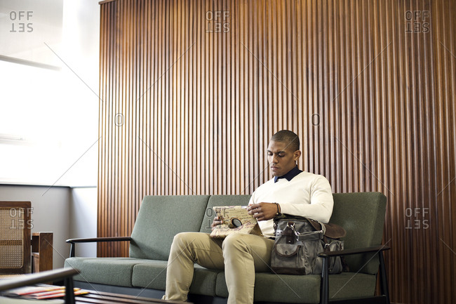 A man sits on a couch and looks at his tablet