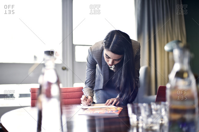 A woman writes a note on a conference table