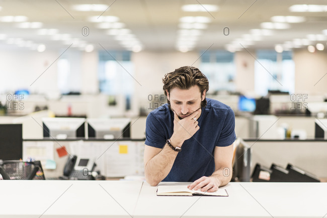 A man leaning on his elbow and looking at an open book on an office desk