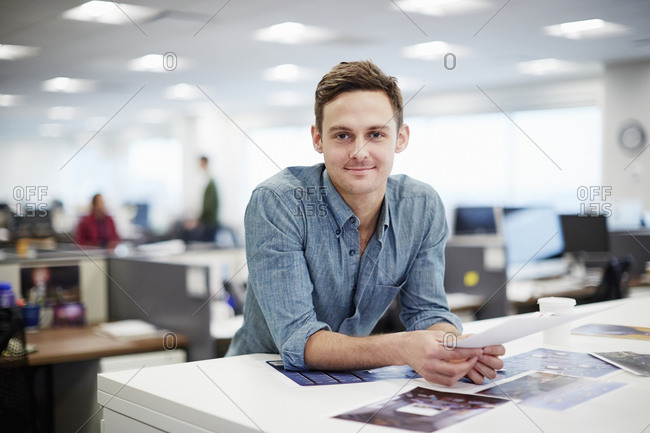 A man smiling and leaning forward on his desk