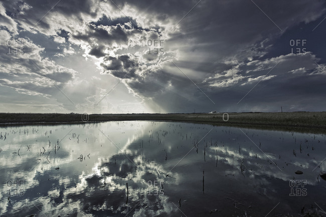 A view to the horizon with clouds and a mirror reflection of the clouds on the water