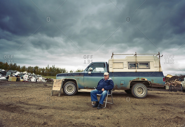 A mature man seated in a chair by his pick up truck surrounded by piles of waste, scrap metal and wooden objects