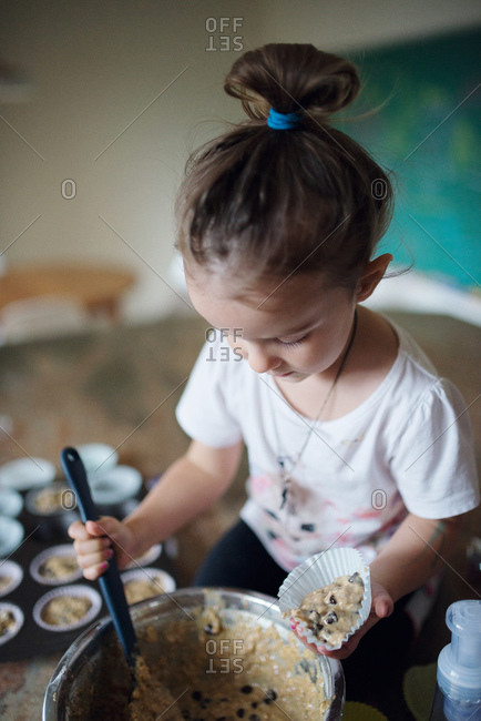 A little girl scoops muffin batter into a wrapper