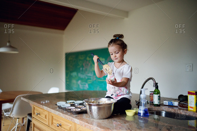 A little girl pours muffin batter into a wrapper