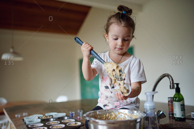 A girl scoops muffin batter into a wrapper