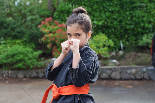 A little girl strikes a martial arts pose