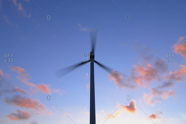 A wind turbine at dusk in Hesse, Germany