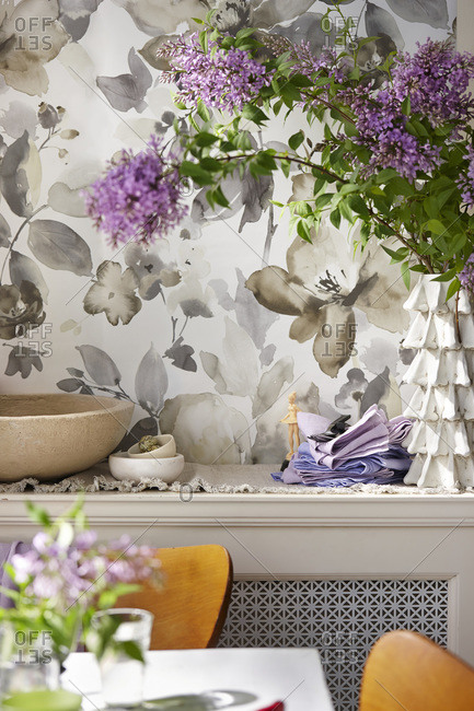 A dining room with bowls, napkins and purple flowers