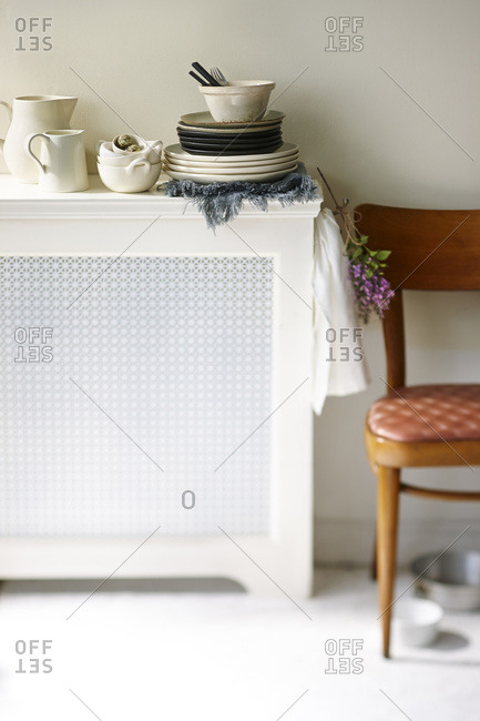 A sideboard in a kitchen with stacks of dishware