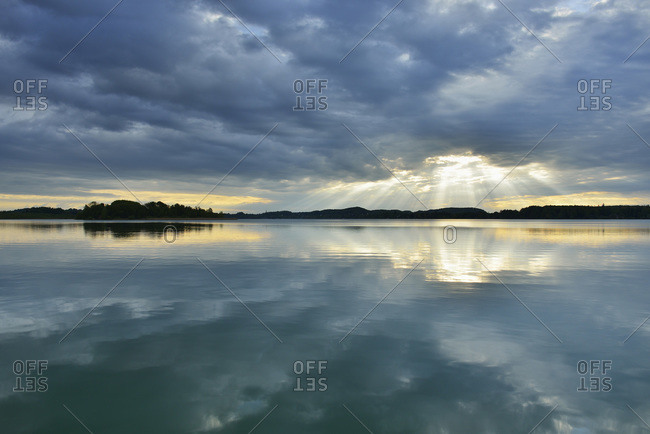 Clouds and crepuscular sunrays reflected in lake at sunrise, Woerthsee Lake, Upper Bavaria, Fuenfseenland, Germany
