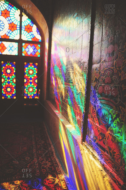 Shiraz, Iran - October 18, 2014: Stained glass window casting colorful lights on the wall of Nasir al-Mulk Mosque