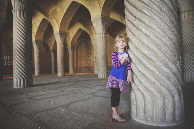Shiraz, Iran - October 18, 2014: Girl leaning against a stone column in the prayer hall of Vakil Mosque