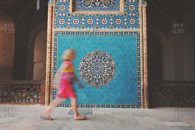 Yazd, Iran - October 20, 2014: Girl walking at the Jameh Mosque of Yazd