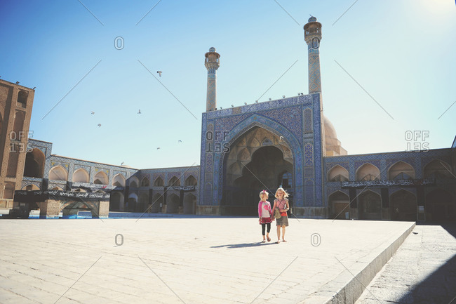 Isfahan, Iran - October 22, 2014: Children walking in the courtyard of the Jameh Mosque of Isfahan