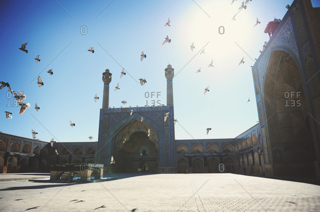 Isfahan, Iran - October 22, 2014: Flock of pigeons fly at the Jameh Mosque of Isfahan
