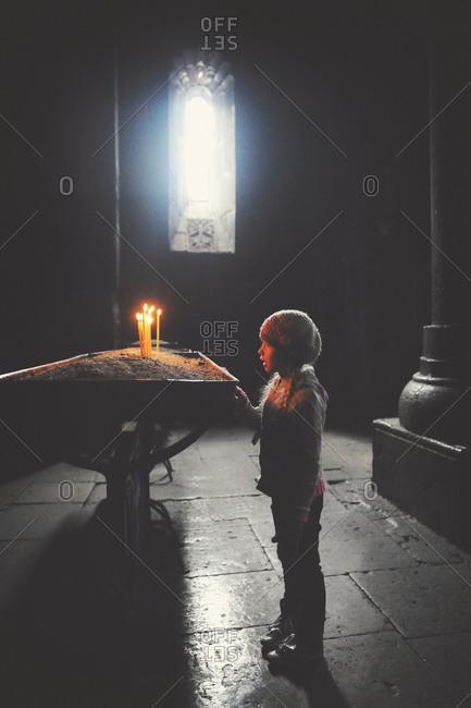 Near Garni, Armenia - November 3, 2014: Girl standing by an altar at the Geghard Monastery