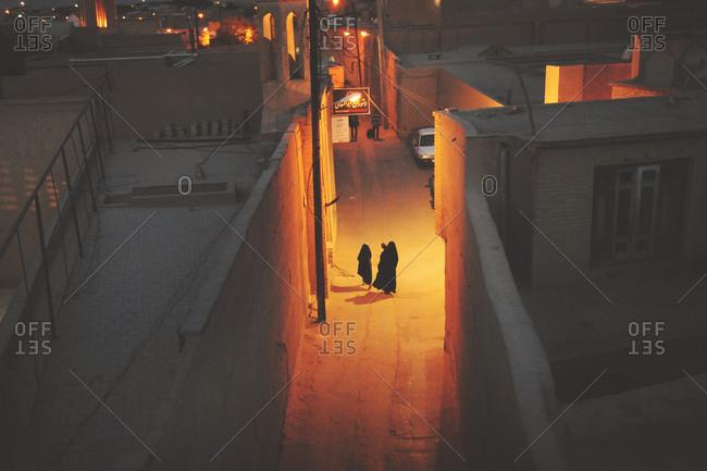 Women walking down a street at night in Yazd, Iran