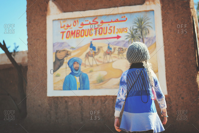 Young girl staring at a poster in Morocco